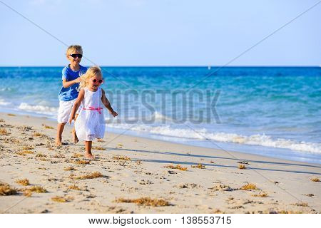 little boy and girl running at beach, family vacation