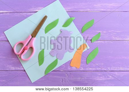 Hippo, leaves, palm tree trunk cut from colored paper. Set to create a summer children cards. Scissors, paper sheet. Hippopotamus and palm tree applique crafts arts idea for kids