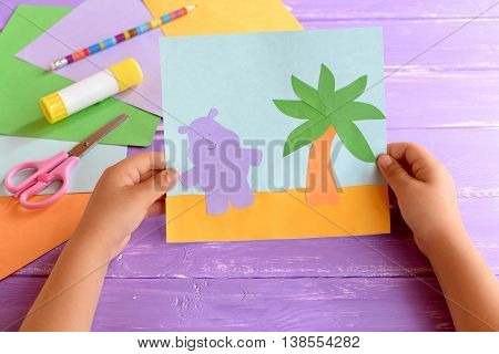 Child holds a paper card with a Hippo and a palm tree. Colored paper sheets, scissors, pencil, glue stick lilac on wooden background. Cute and easy hand craft for preschoolers