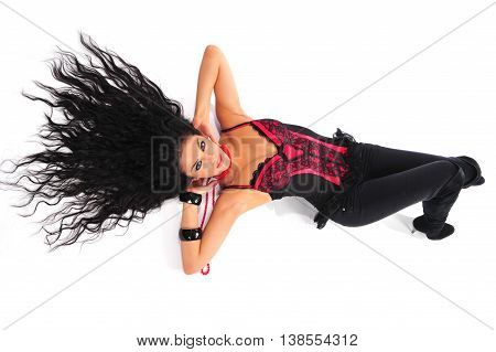 Sexy brunette in red corset with long hair spreading out lying down on a floor