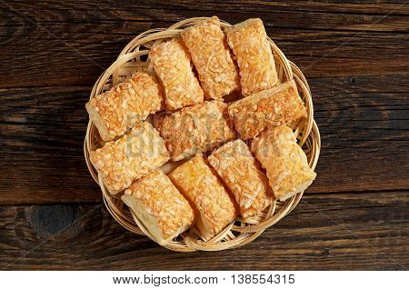 Puff biscuits with cheese in wicker plate on wooden background top view