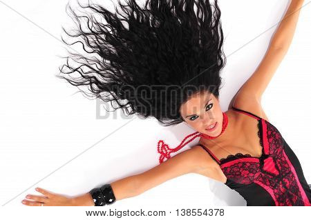 Sexy brunette in red corset with long hair and hands spreading out lying down on a floor