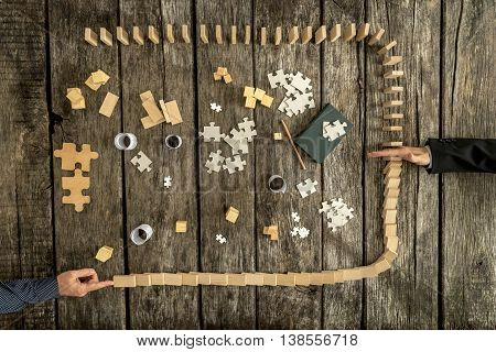 Top down view on hand blocking falling dominos surrounding puzzle pieces over wooden table background for concept about competition management and business problems.