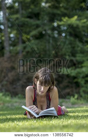 Single adult woman in sleeveless top laying down on grass reading a book with copy space over trees.