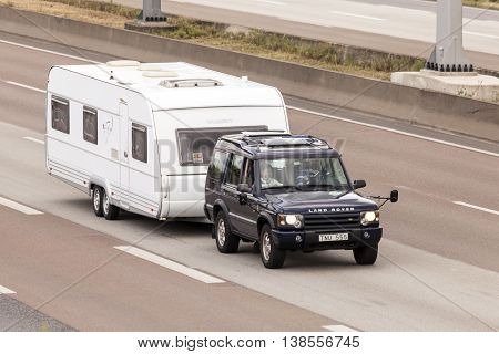 FRANKFURT GERMANY - JULY 12 2016: Land Rover Discovery with a caravan driving on the highway in Germany