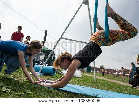 Saint-Petersburg, Russia - June 26, 2016: Yoga instructor conducts a trial lesson for aerial yoga in hammocks during the celebration of the World Yoga Day