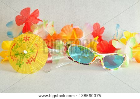 A colorful flower garland displayed with a cocktail umbrella and glasses  on a white background