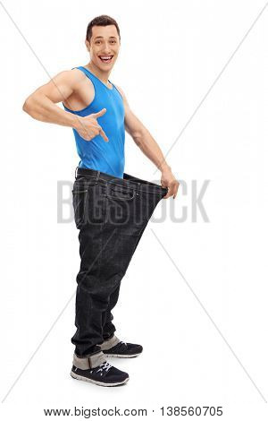 Full length vertical shot of a young handsome guy showing his old oversized jeans isolated on white background
