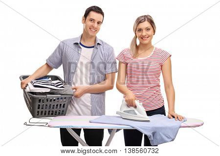 Young man helping his girlfriend with ironing clothes isolated on white background