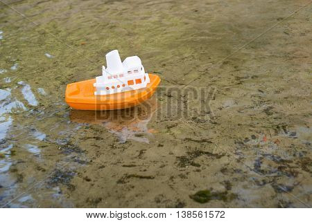 Toy boat floating on the clear water of the river on a Sunny day.