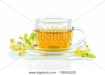 Infusion of linden tree with flowers in a glass cup isolated on white background
