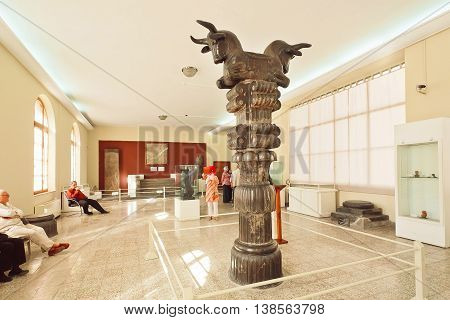 TEHRAN, IRAN - OCTOBER 6, 2014: Carved column from ancient Persepolis and some tourists inside the National Museum on October 6, 2014. Established in 1937 museum contain artifacts from Achaemenid period.