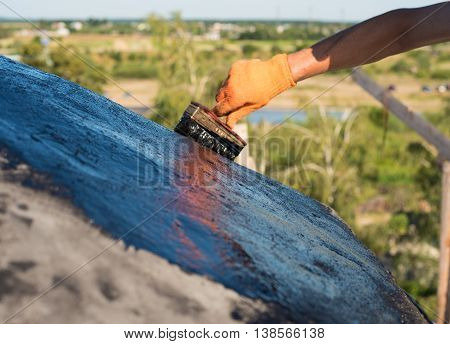 Roofer cover the concrete base polymer modified bitumen waterproofing primer. A worker brushes cover concrete bitumen-rubber primer.
