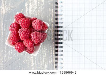 Fresh Raspberries And Blank Notebook
