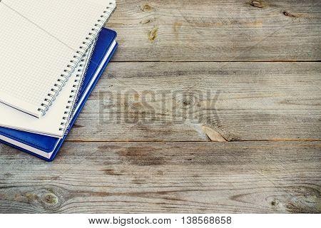 Still life, business, education concept. Stack of notebooks on a rustic wooden table. Selective focus, copy space, school background, top view, toned
