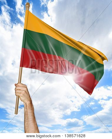 Person's hand holding the Lithuanian national flag and waving it in the sky, 3D rendering