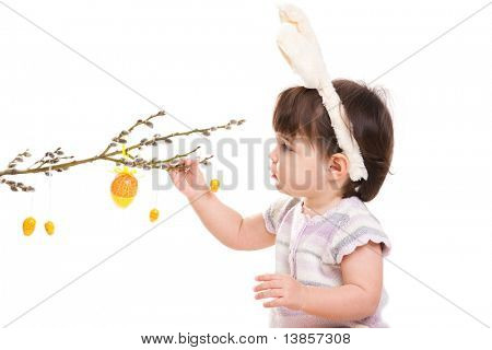 Baby girl in easter bunny costume, playing with easter eggs hanging from willow branch. Isolated on white background.?