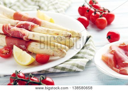 Fresh White Asparagus Wrapped In Jamon On A Blue Wooden Table