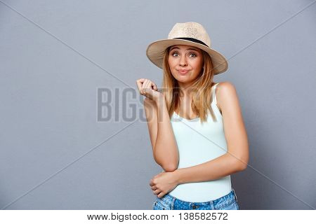 Portrait of young beautiful girl in hat feeling shame, looking at camera over gray background. Copy space.