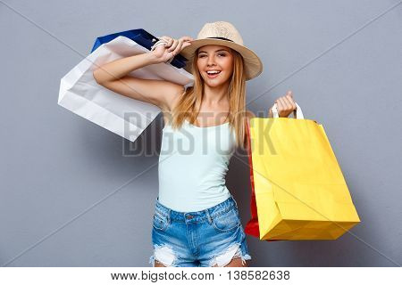 Portrait of young beautiful girl in hat smiling, winking, looking at camera, holding packages with clothing over gray background.