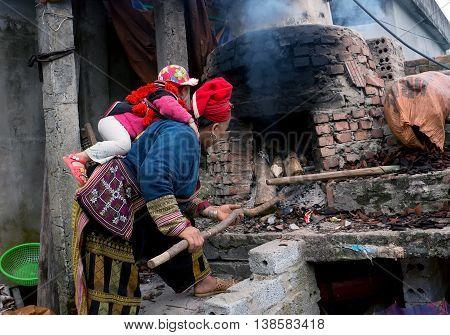 SAPA, VIETNAM, February 12, 2016 the mother and baby ethnic Dao, highland Sa Pa, Vietnam. modular kitchen fire