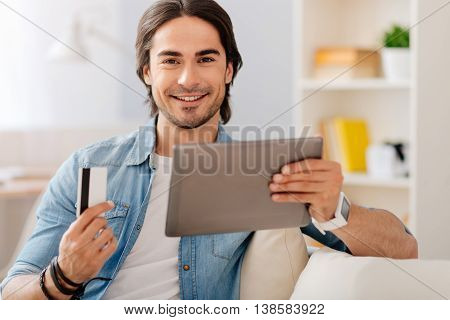 Make your life easier. Cheerful bearded handsome smiling man holding credit card and using tablet while sitting on the couch