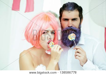 young glamour couple of pretty woman with orange hair and bearded handsome man with blue beard eating lollipop candies