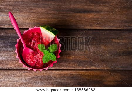 Homemade sorbet of watermelon on a dark wooden background. Selective focus.