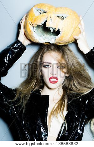 Young sexy woman with bright glamour makeup on pretty face and beautiful hair in black leather coat holding scary halloween pumpkin on grey background