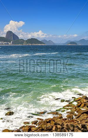 Copacabana Beach in Rio de Janeiro with its buildings sea sand and the Sugar Loaf hill in the background