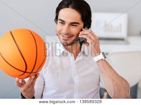Nice to hear you. Positive handsome smiling man talking on cell phone and holding basket ball