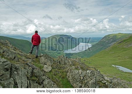 Man overlooks Wasdale Head and Wast Water from Beck Head on the slopes of Great Gable mountain in the English Lake District National Park.