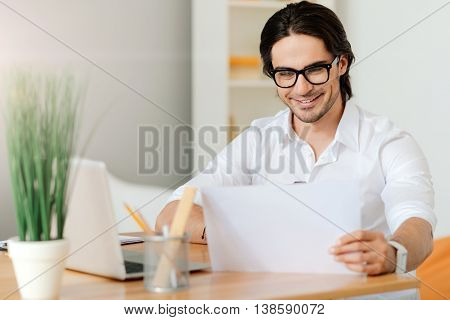 Work with pleasure. Joyful delighted handsome an sitting at the table and using laptop while working in the office
