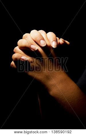 a woman deeply praying with folded hands