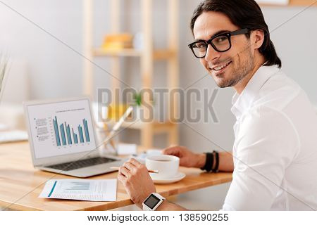 Real workaholic. Delighted bearded handsome man smiling and working with papers while drinking coffee