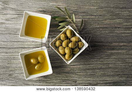 Olive oil with fresh olives on wooden background