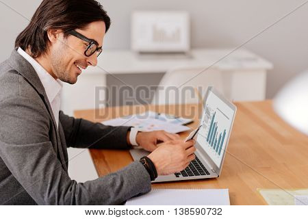Joy in mind. Overjoyed smiling handsome man sitting at the table and holding credit card while using laptop