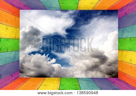 multicilored frame on the dark blue sky background with great white clouds