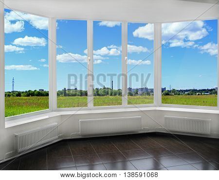 room with modern interior window to the summer field and view of tubes of city