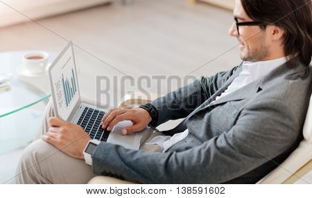 Modern user. Cheerful pleasant bearded man sitting in the chair and using laptop while being involved in work