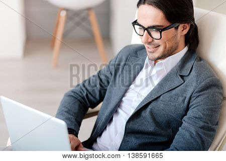 In pace with time. Pleasant delighted handsome businessman sitting in the chair and expressing positivity while using laptop