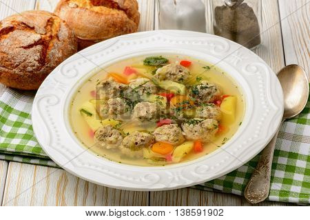 Soup with meatballs on white wooden background.