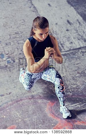Athletic woman warming up doing weighted lunges in urban environment. Workout exercise for butt legs on the street. Healthy lifestyle sport bodybuilding concept.
