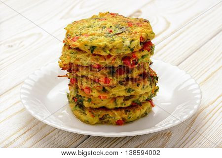 Vegetarian cuisine - vegetable fritters (with potatoes, carrot, zucchini, paprika and parsley).
