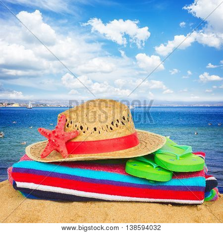 sunbathing accessories and straw hat on sand by seaside