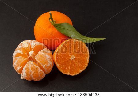 Tangerines on black background. Food concept photo