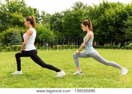 Take care of your health. Pleasant slim beautiful women standing on the grass and stretching while doing sport exercises