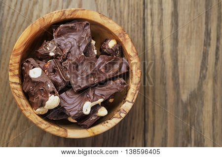 broken homemade bar of chocolate with cashew nuts in wood bowl, shallow depth of field