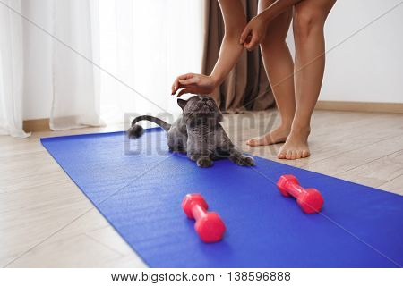 Young fitness woman stroking a cat on yoga-mat