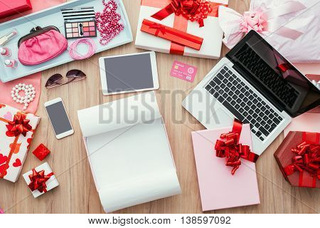 Open empty gift box on a desktop with a laptop a credit card and beauty accessories online shopping and fashion concept